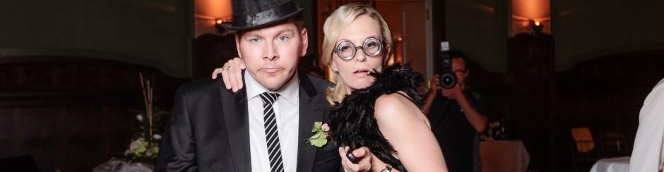 Zwei Personen stehen vor der Fotobox und umarmen sich. Der Mann trägt einen Zylinder und die Frau trägt eine Nerdbrille.